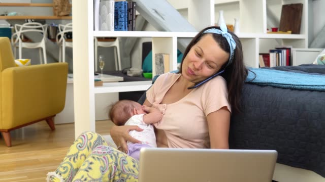 Young woman breastfeeding her baby and working from home