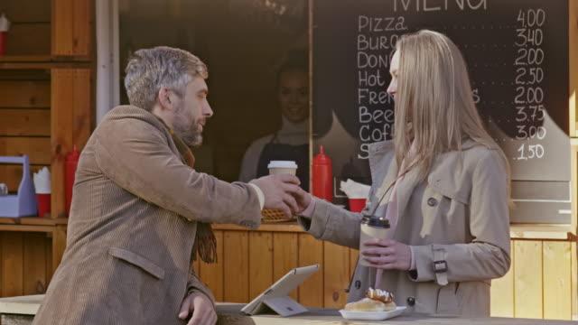 ung kvinna föra kaffe man genom mat monter - mature women studio grey hair bildbanksvideor och videomaterial från bakom kulisserna