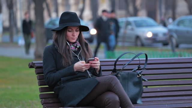 ブラウズ若い女性彼女のスマートフォンで音楽を聴きながら、街の一日の終わりには、ます。 - ベンチ点の映像素材/bロール