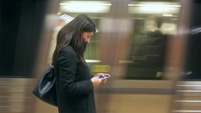 vídeos de stock, filmes e b-roll de jovem mulher navegando seu smartphone na estação de metrô. - escolher