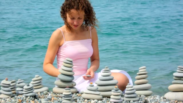 Young woman building stone stack on pebble beach video