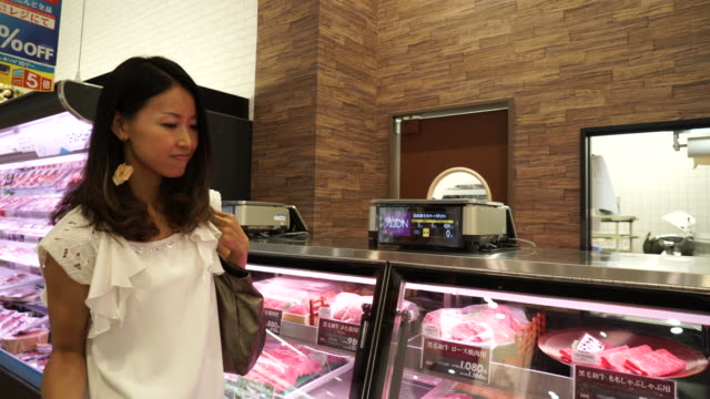 Young woman butcher is measure the meat video