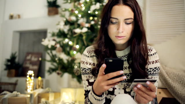 Young woman buying gifts with credit card on Christmas at home video