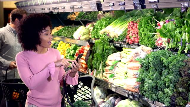 junge frau kauft lebensmittel, einkaufsliste am telefon - grünkohl stock-videos und b-roll-filmmaterial
