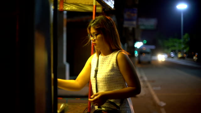 Young Woman buying in street stall at night video