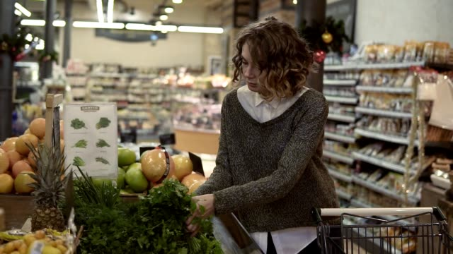 Young woman buying Ooganic food in supermarket. Female taking green fresh parsley in grocery store. Choosing good pale. Slow motion. Healthy Lifestyle Concept video