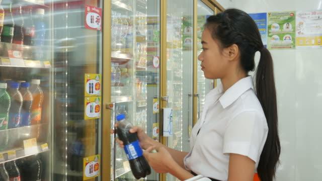 Junge Frau, die gekühlte Lebensmittel Produkt im Kühlregal zu kaufen – Video