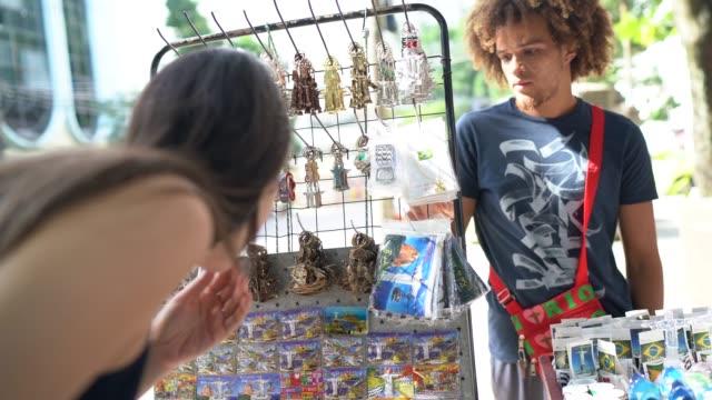 yerel pazar sokakta hediyelik eşya satın genç kadın - pazarcı stok videoları ve detay görüntü çekimi