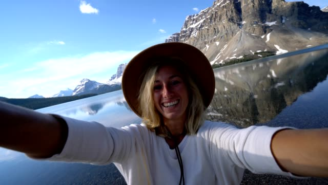 Young woman by the lake takes selfie surrounded by nature video