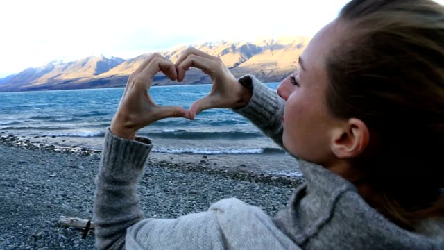 Young woman by the lakeshore makes a heart shape finger frame on mountain lake landscape Young woman by the lakeshore makes a heart shape finger frame on mountain lake landscape. Love concept. oceania stock videos & royalty-free footage