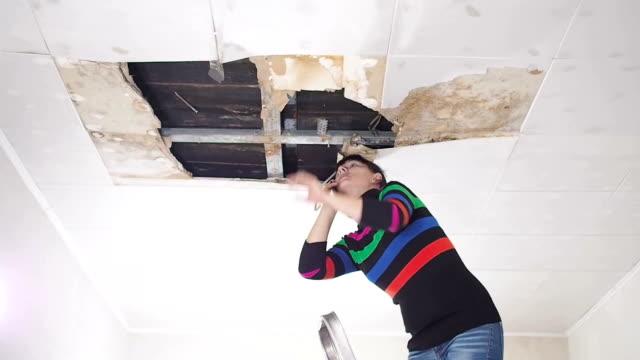vidéos et rushes de appel de la jeune femme au téléphone dans le service et les services publics. panneaux de plafond endommagés énorme trou dans le toit de la fuite de l'eau de pluie. endommagés par l'eau cas au plafond, de l'assurance. - endommagé