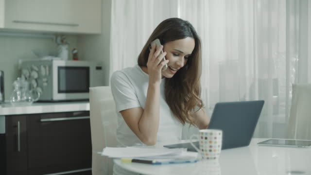 Young woman call phone at home kitchen. Business woman talking mobile phone