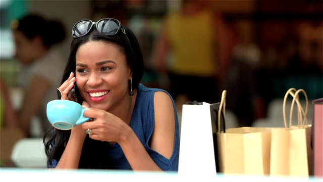Young woman calling a friend while having a coffee video