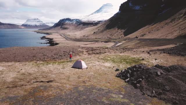 vídeos de stock e filmes b-roll de young woman camping near the ocean in iceland, aerial view - berma da estrada