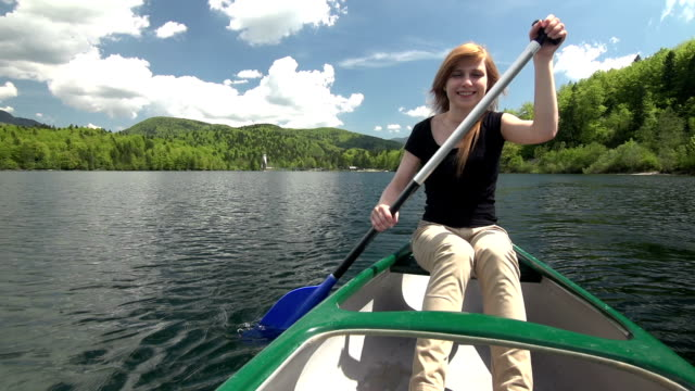 Young woman canoeing on a lake in the mountainside video