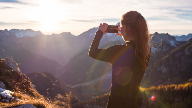 Young woman capturing memories with her smartphone from a mountain video