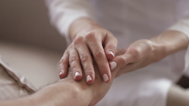 Young woman caregiver holding hand of old man, closeup view