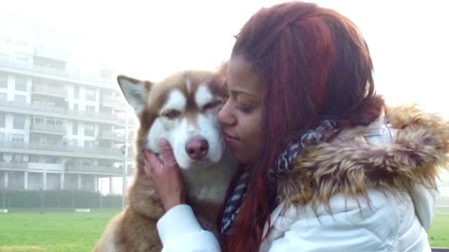 giovane donna accarezzi il suo cane-rallentatore - malamute video stock e b–roll