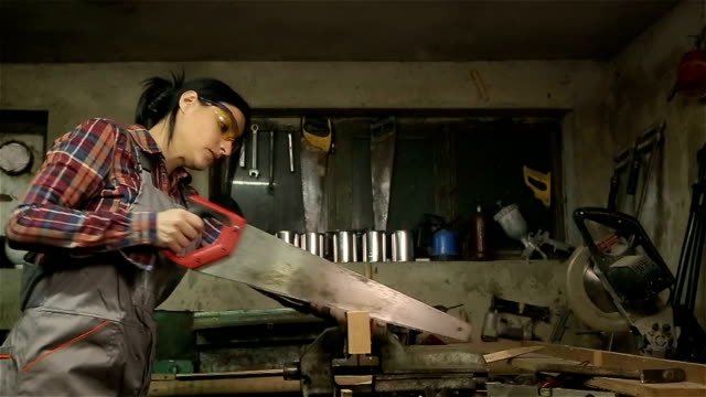 Young woman carpenter cutting a board whit saw video