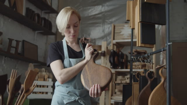 Young woman carpenter examines handmade wooden cutting board Young woman carpenter examines wooden handmade cutting board in her woodworking workshop. Slow motion close up shot. carpentry stock videos & royalty-free footage