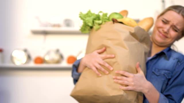 vídeos y material grabado en eventos de stock de mujer joven que lleva una bolsa de papel pesada con productos de la tienda, necesita entrega - pesado