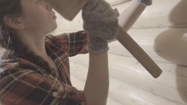 stockvideo's en b-roll-footage met jonge vrouw die houten logboeken met oakum dichtstuleert en verzegelt. de mooie vrouw werkt binnen het houten gebouw en werkt met hamer. niet-gedegradeerde versie, platte kleurprofiel - boomstam