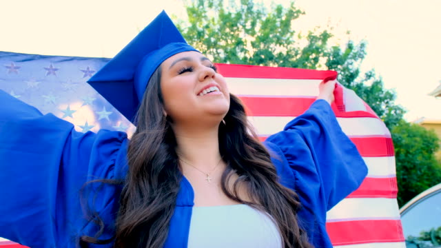 Young woman celebrating her graduation holding a US flag