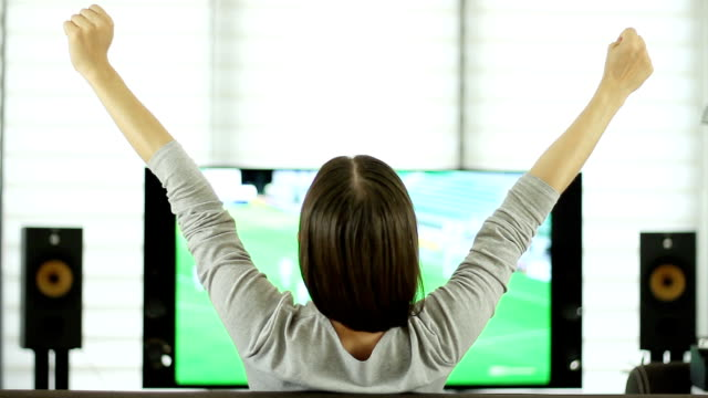 Young woman celebrating soccer goal, rear view video