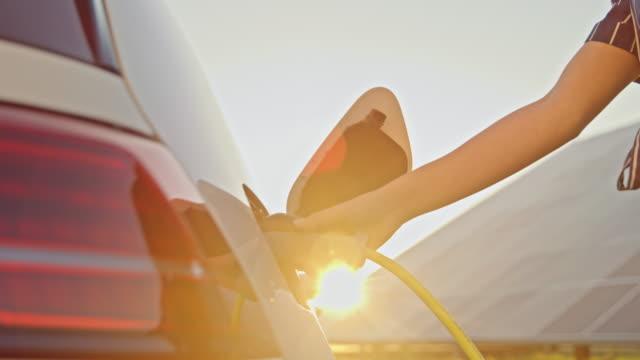 slo mo giovane donna che carica la sua auto con una potenza dai pannelli solari - carica elettricità video stock e b–roll