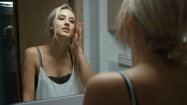 Young woman checking her face in bathroom mirror at home.