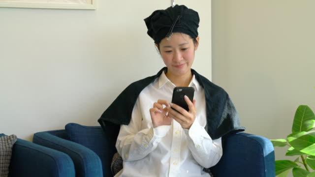 若い女性の髪の乾燥を待っている間に美容室で彼女の携帯電話をチェック - 美容院点の映像素材/bロール