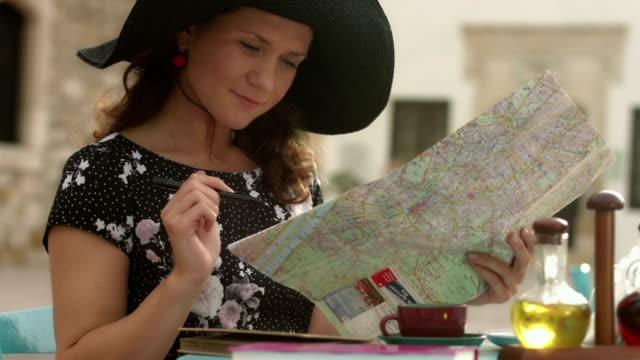 junge frau, die karte, zufrieden mit reise planen, machen notizen - kartographie stock-videos und b-roll-filmmaterial