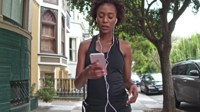 Young Woman checking mobile phone app after running outdoors in San Francisco