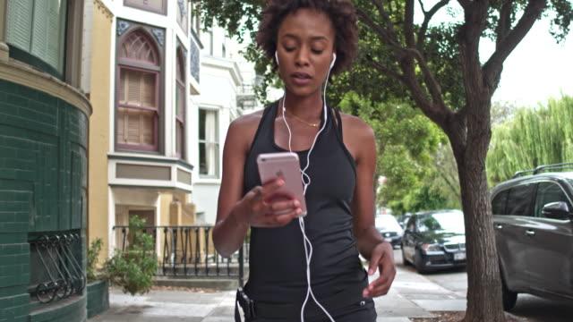 샌 프란 시스 코에서 야외에서 실행 한 후 휴대 전화 애플 리 케이 션을 확인 하는 젊은 여자 - wellness 스톡 비디오 및 b-롤 화면