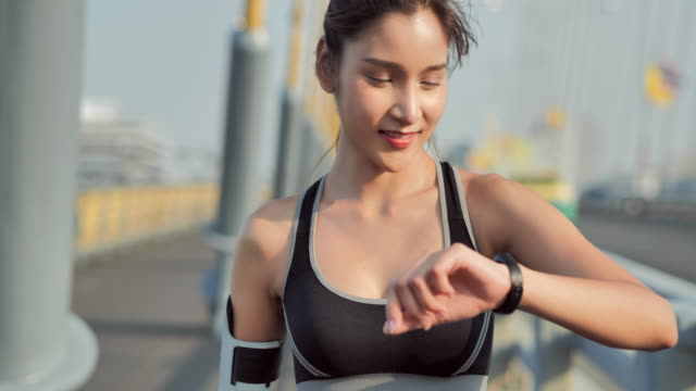Young woman checking progress on smart watch.Female runner looking at smart watch heart rate monitor.Lifestyle,Success,Power,Healthy,Technology,Women in Sport.Sport Prep.People on Modern Technology - vídeo
