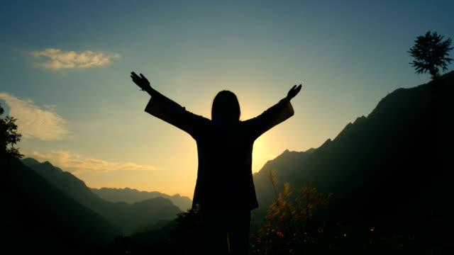 young woman cheerful on top of the mountain - podnosić filmów i materiałów b-roll