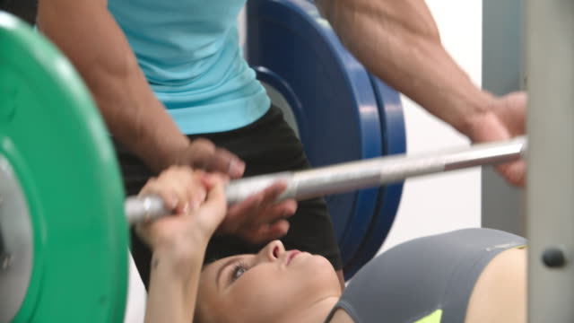 Young woman chest pressing barbells with a trainer at a gym video