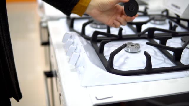 vídeos de stock e filmes b-roll de a young woman chooses a gas stove in a home appliance store. - cooker happy