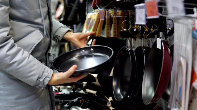 a young woman chooses a non-stick frying pan in the store. - garnek filmów i materiałów b-roll