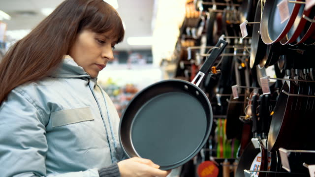 A young woman chooses a pan at the store. Customer woman's selects a pan with non-stick coating in the tableware section of the hypermarket. cooking pan stock videos & royalty-free footage