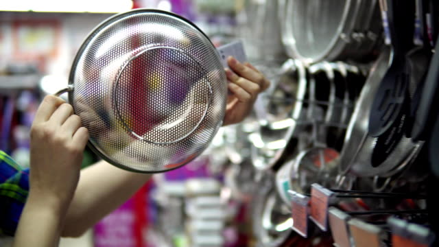A young woman chooses and buys a colander in the supermarket. video