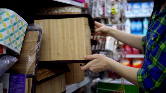 a young woman chooses and buys a folding box for things in the supermarket. - cestino video stock e b–roll
