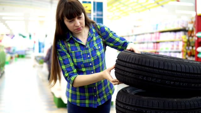 A young woman chooses and buys car tires at the supermarket . A young woman in a blue checkered shirt chooses and buys car tires at the supermarket in the department of automotive goods. tires stock videos & royalty-free footage