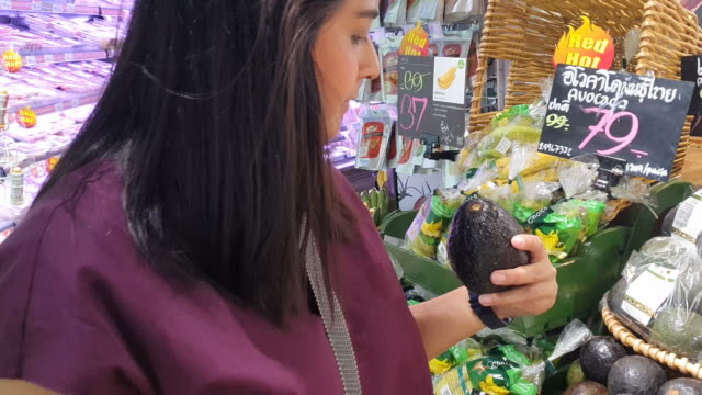 Young woman chooses avocado and Shopping in supermarket