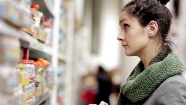 Young woman chooses baby food in the supermarket video