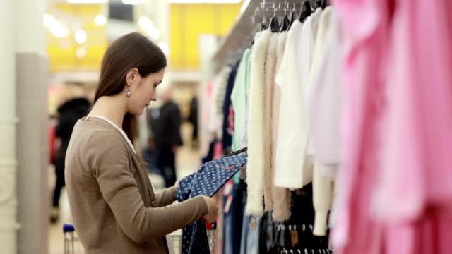 vídeos y material grabado en eventos de stock de mujer joven elige ropa para un niño - eventos de etiqueta