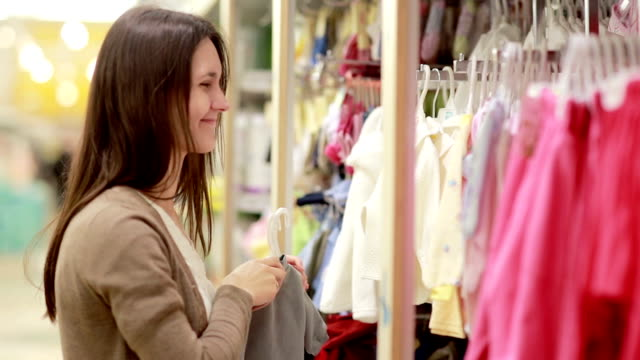 young woman chooses clothes for newborn baby video