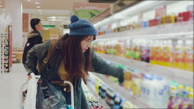 Young woman chooses dairy produce in the store video