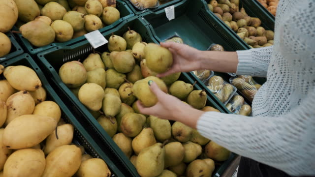 Young woman chooses green pears at the market. Girl's hands close-up.