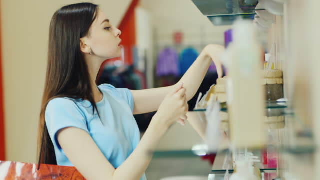 junge frau wählt elemente in der parfüm-abteilung am telefon sprechen - kosmetik beratung stock-videos und b-roll-filmmaterial